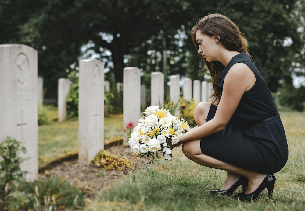 widow visiting her husband's grave after filing a wrongful death claim with a wrongful death lawyer